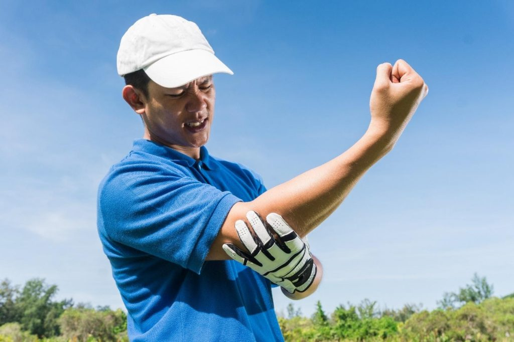 golfer massaging his righ elbow